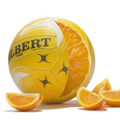 Photo composite image of a netball sliced open to reveal the inside is made of an orange.